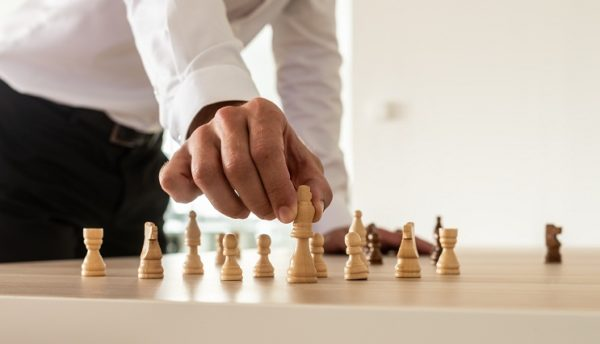 Business leadership concept - businessman standing at his office desk placing chess figures on table with the king in front.